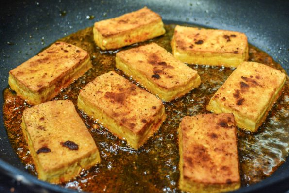 Tofu frying in a pan